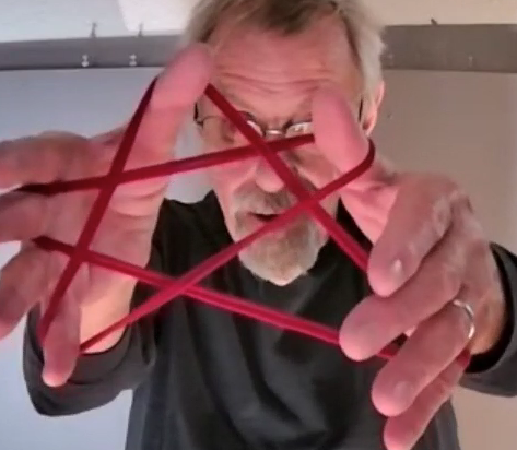 Fred holds a red string in the shape of a 5 pointed star very close to the camera